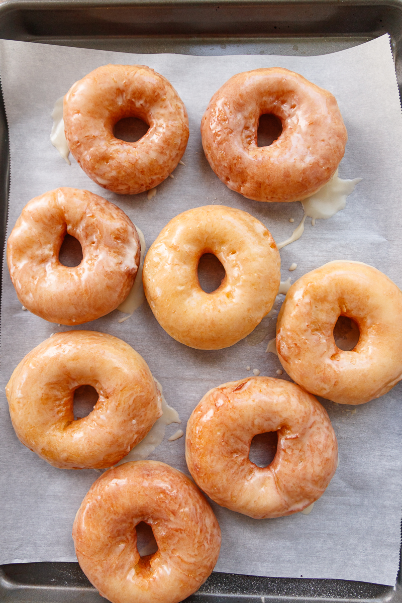 top view of the sourdough discard donuts on a parchment paper-lined baking sheet