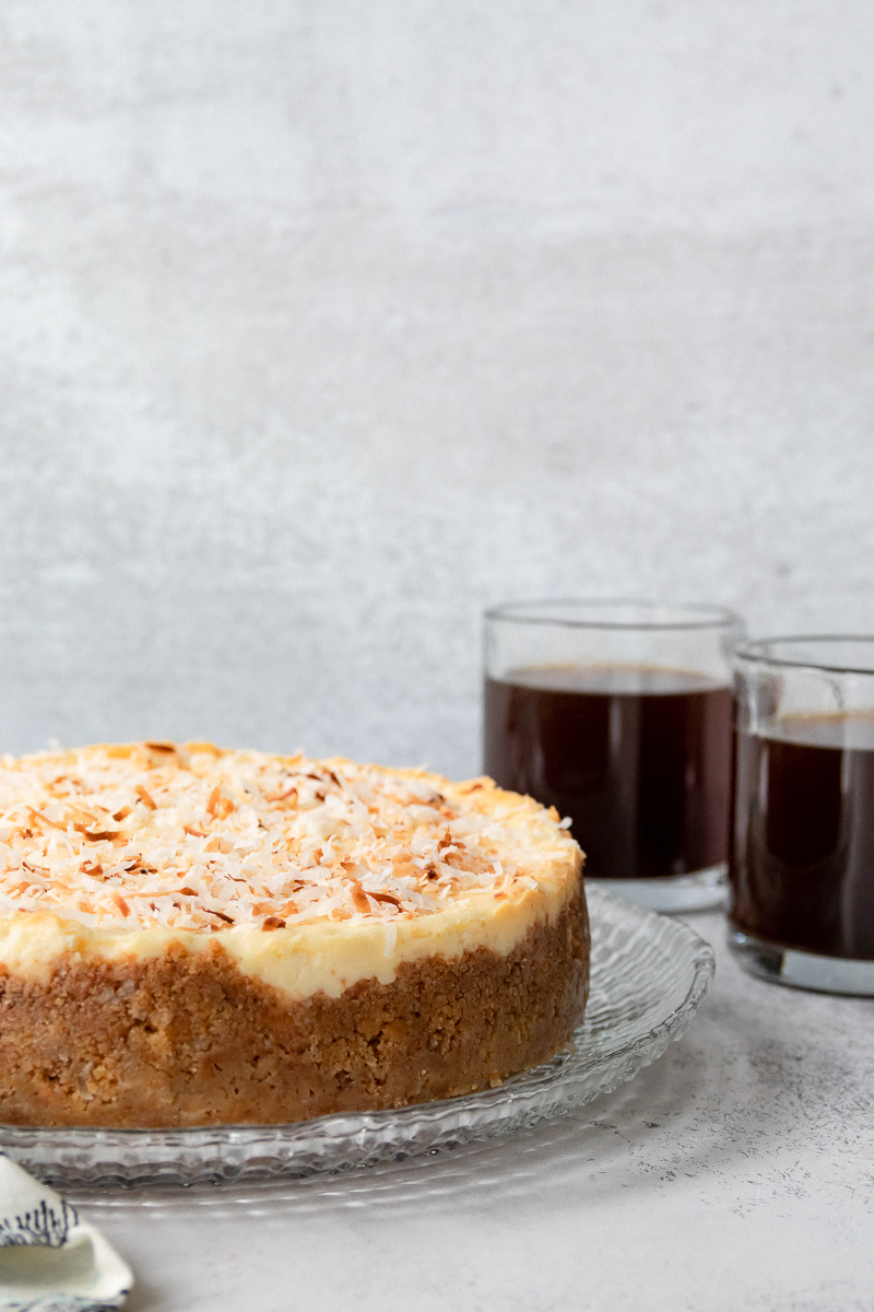toasted coconut cheesecake with coffee in the background