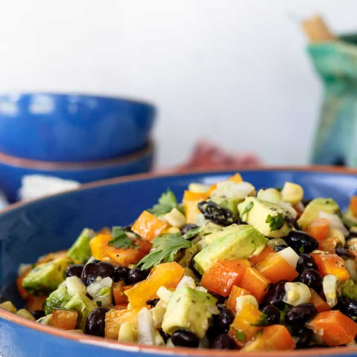 close up of the corn and black bean salad in a blue serving bowl
