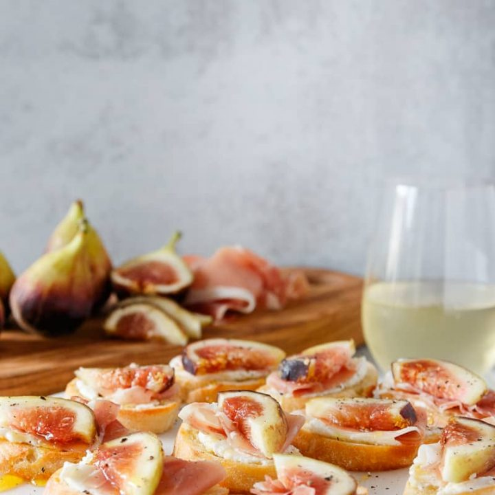 fig crostini on a marble tray with a glass of white wine and more fresh figs in the background