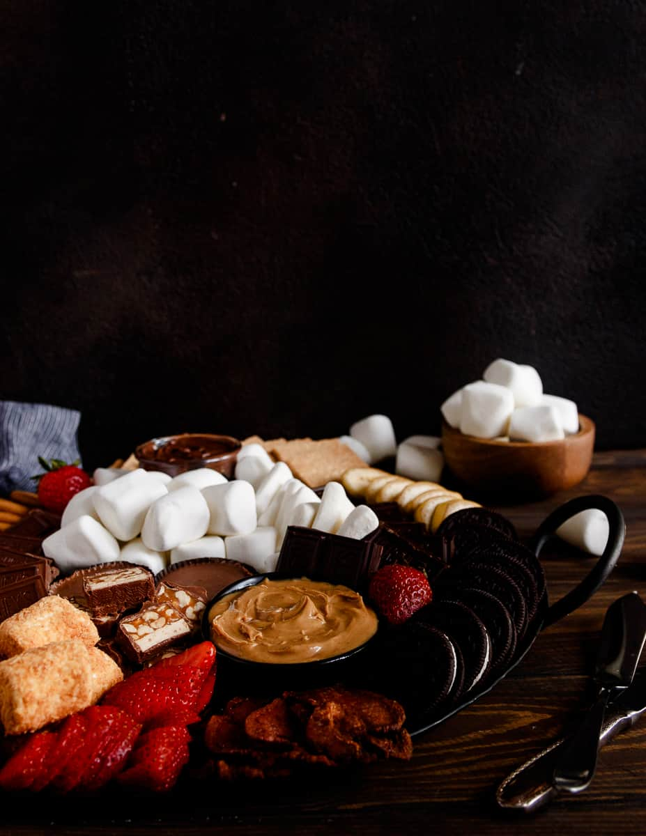 smores board on a wooden table with a black background