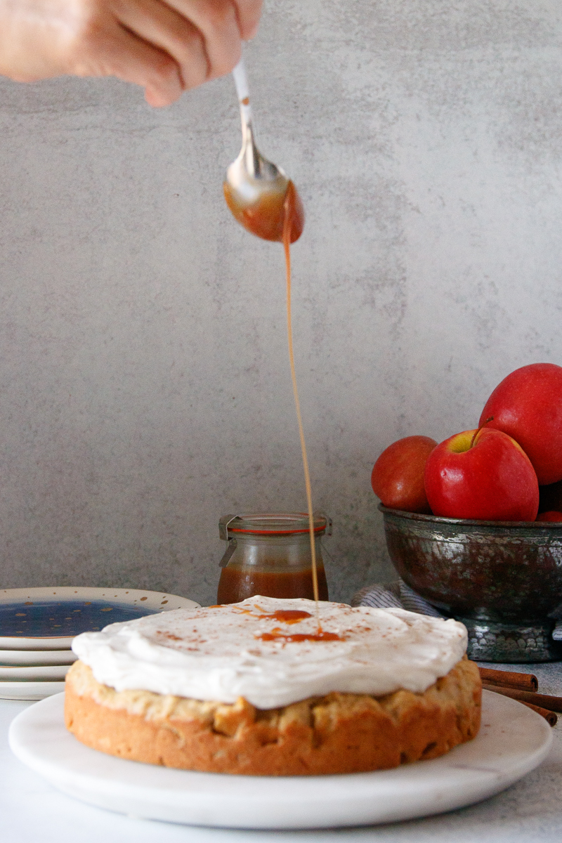 spoon drizzling caramel on a frosted apple breakfast cake