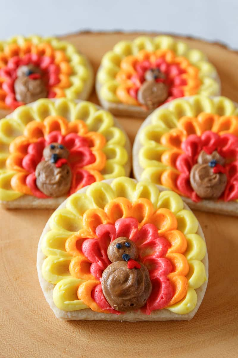 easy turkey cookies decorated with buttercream frosting and arranged on a wood serving platter