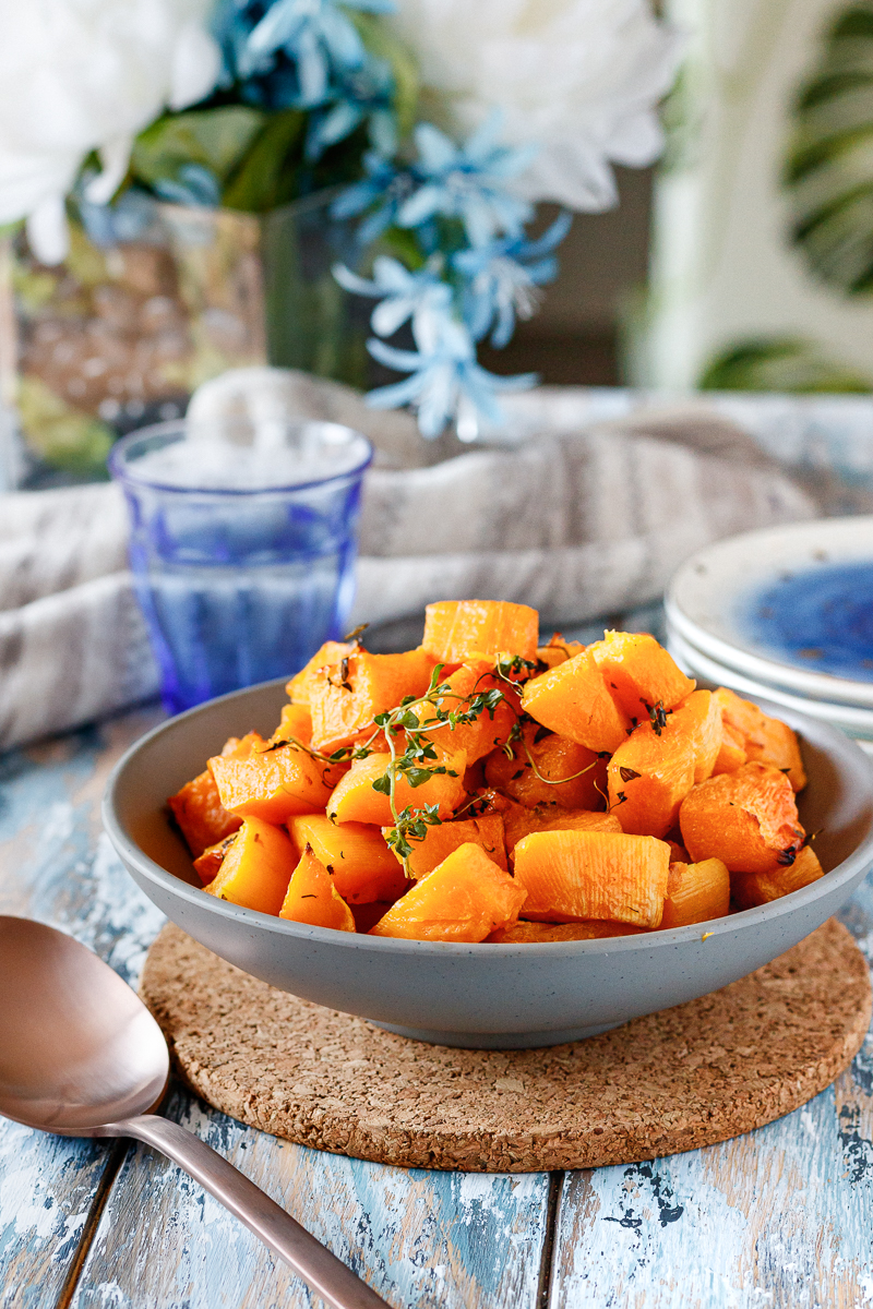 bowl of butternut squash on a styled table with blue tones and a leaf-print chair in the background