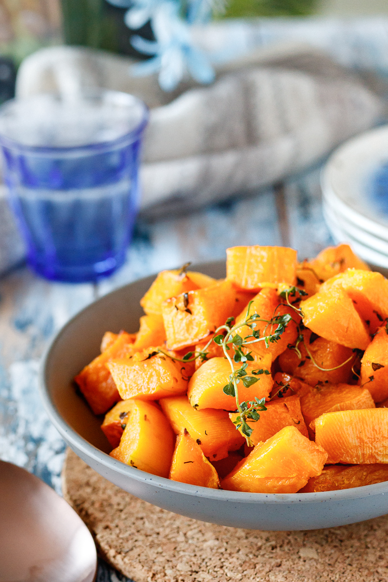 lemon thyme roasted butternut squash ready to serve in a grey bowl