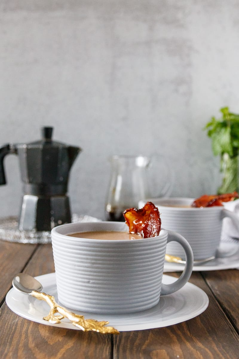maple bacon latte in a grey textured mug with a slice of maple candied bacon as garnish