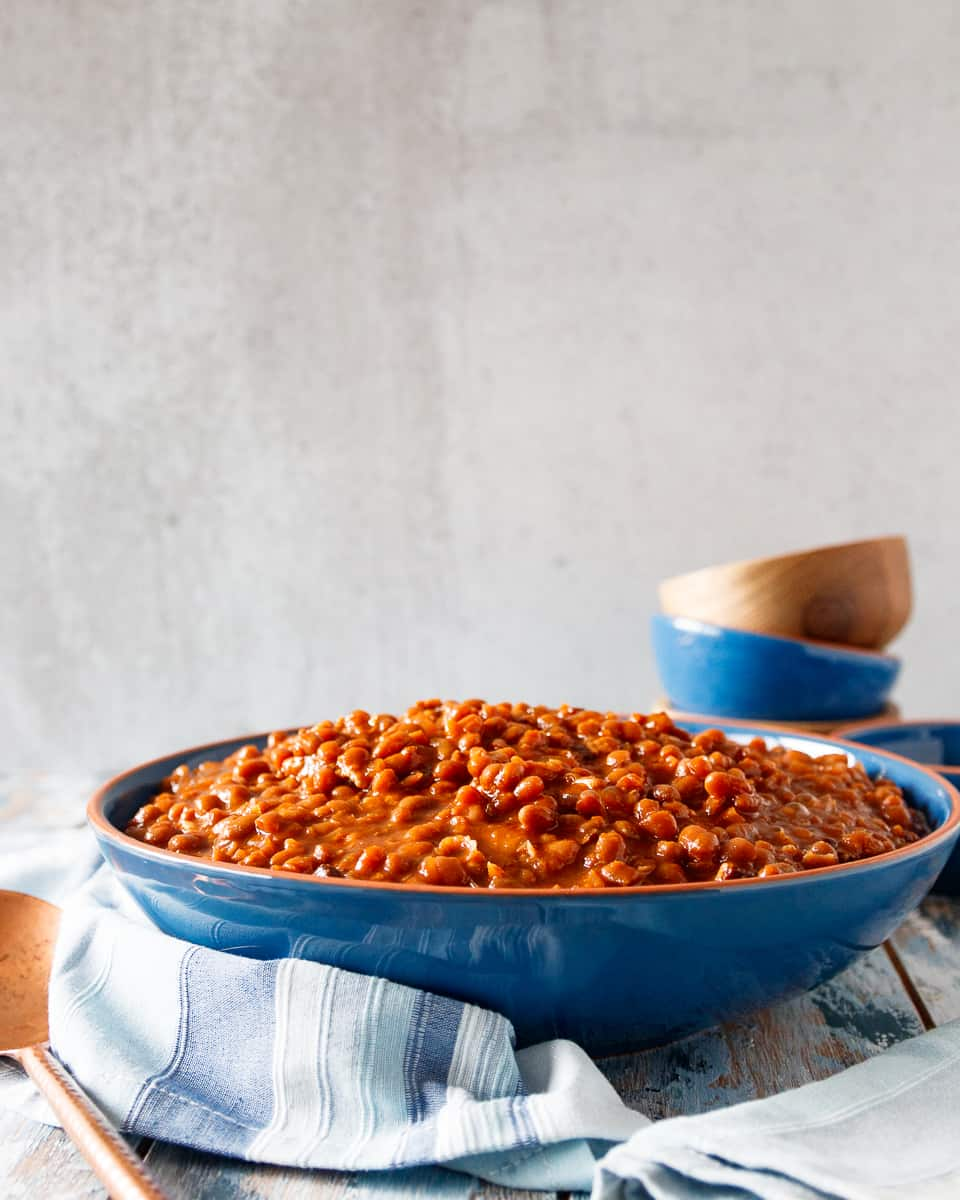 slow cooker baked beans in a blue bowl with a light grey background. Blue and wooden bowls stacked in the background