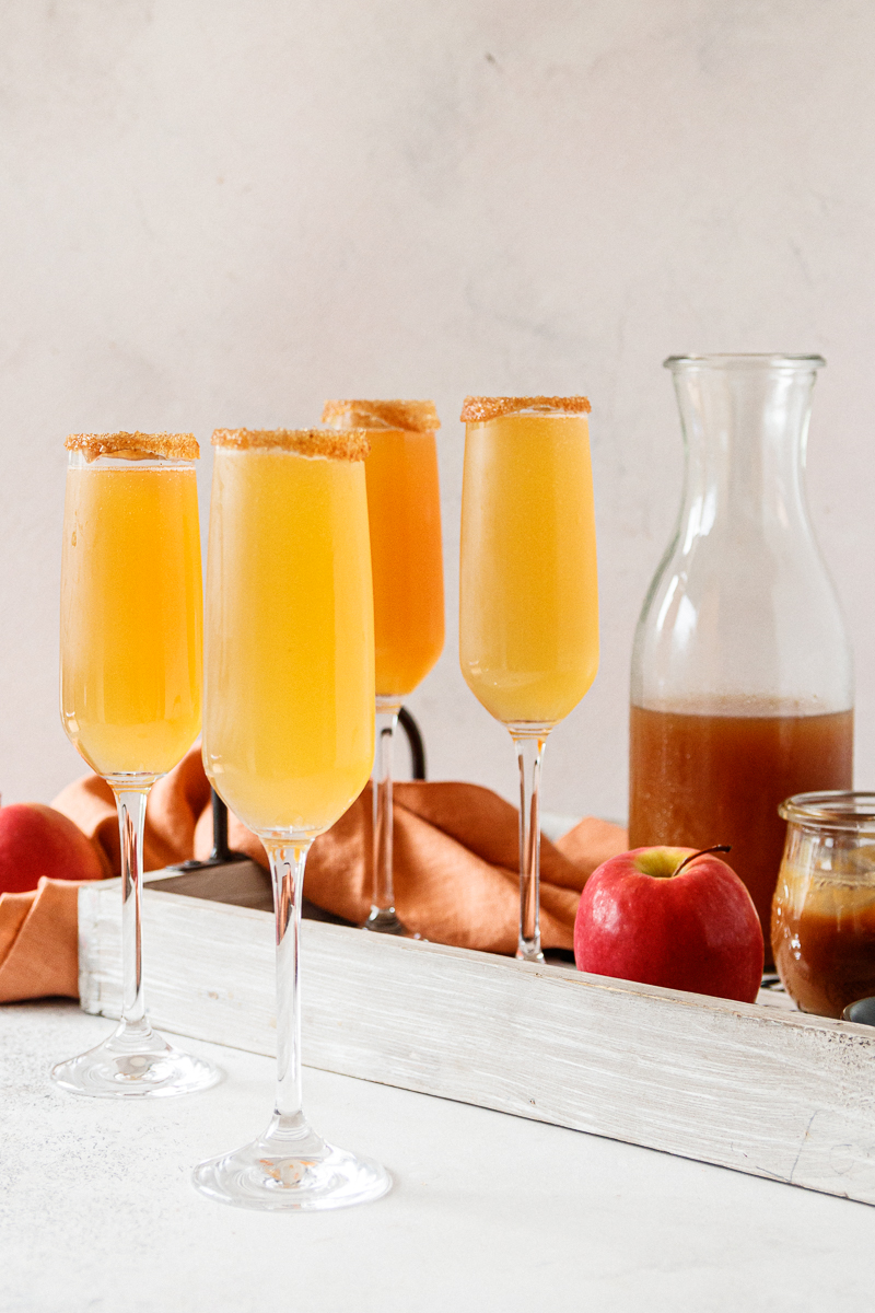 caramel apple cider mimosas shown ready to serve with a light wooden tray in the background