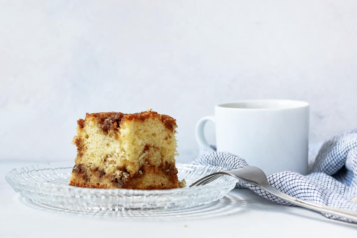 slice of easy sour cream coffee cake on a glass plate with a white mug of coffee in the background