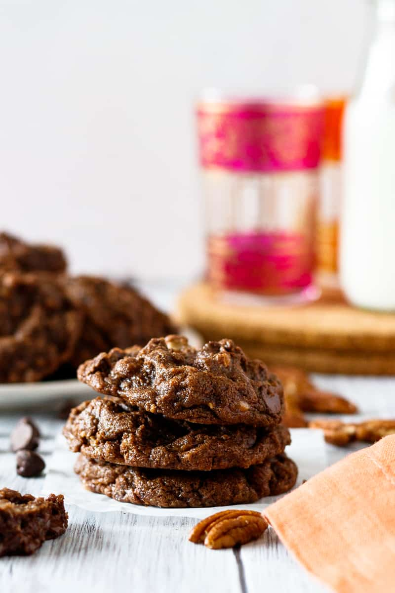 double chocolate pecan toffee cookies stacked with a platter in the background