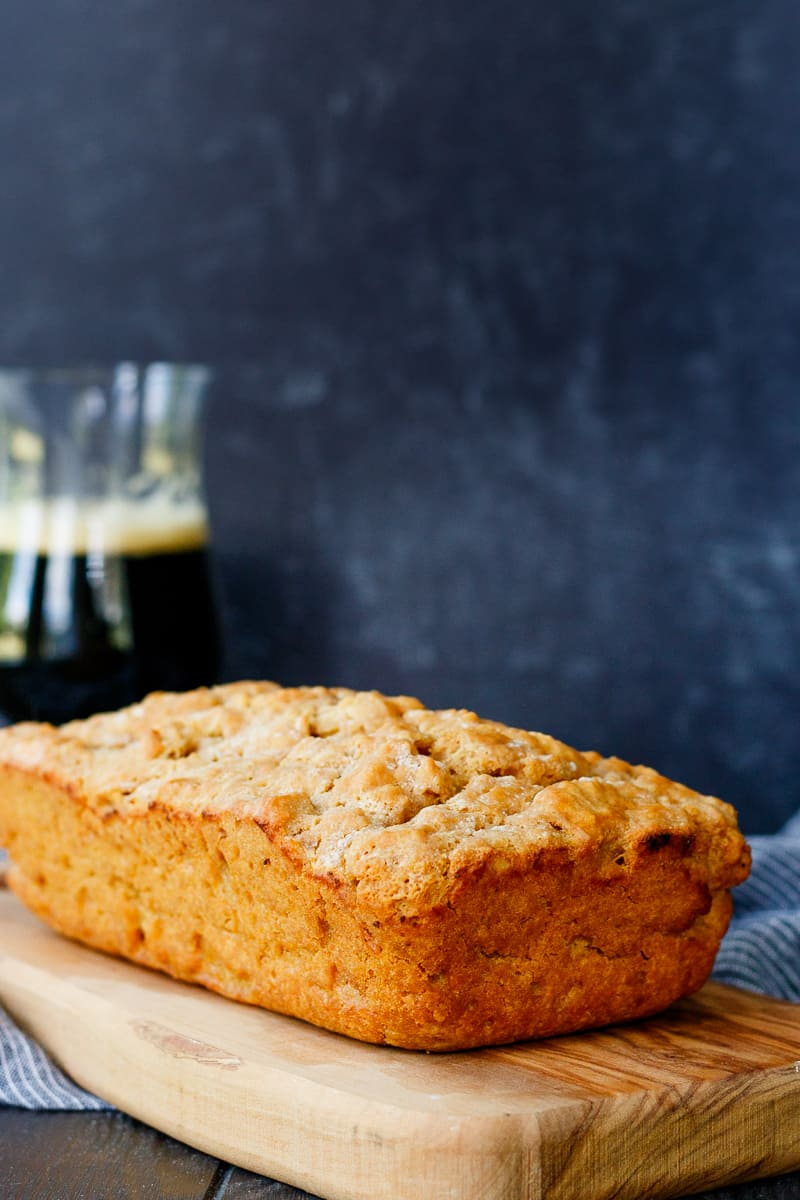 loaf of beer bread on a cutting board with a darker background and glass of beer towards the rear left of the photo