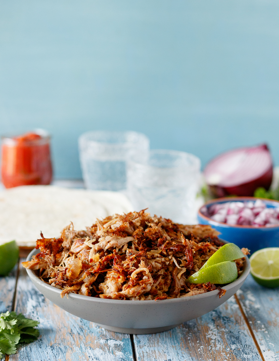 Easy slow cooker carnitas in a grey bowl with lime wedges for serving