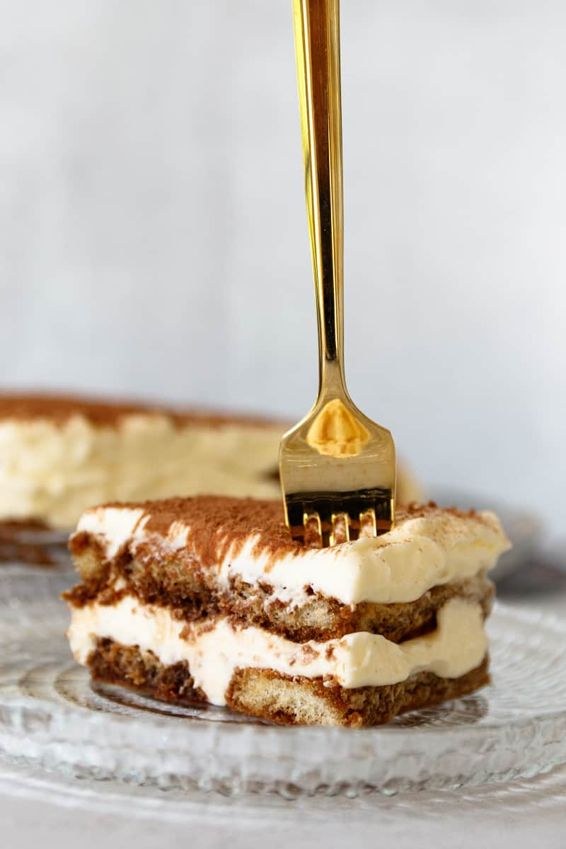golden fork vertically positioned in a slice of tiramisu, poised to break off a piece