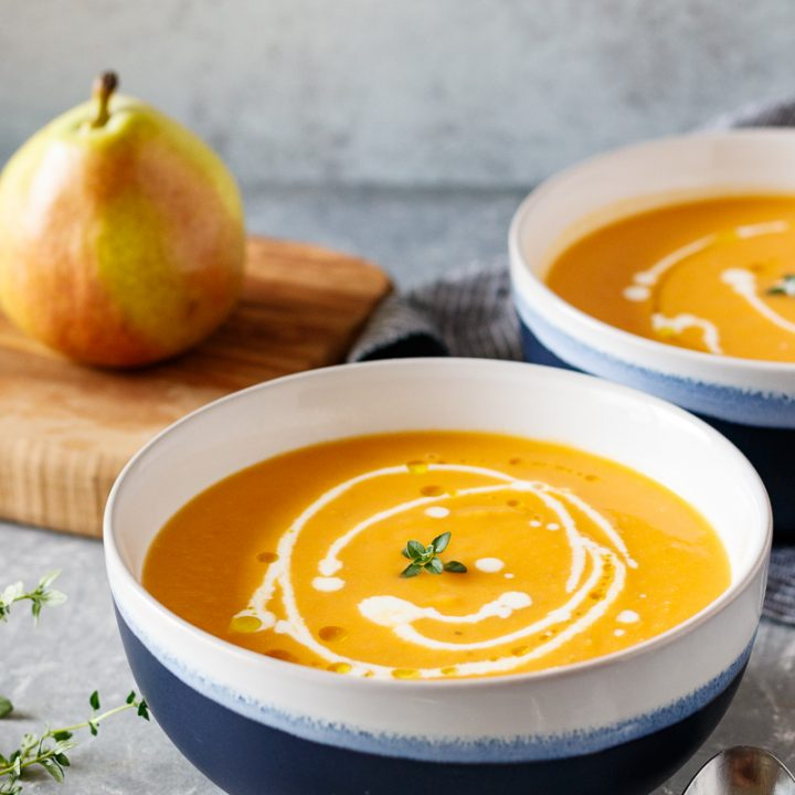 pear and sweet potato soup in blue and white bowls with a drizzle of heavy cream to add fancy detailing