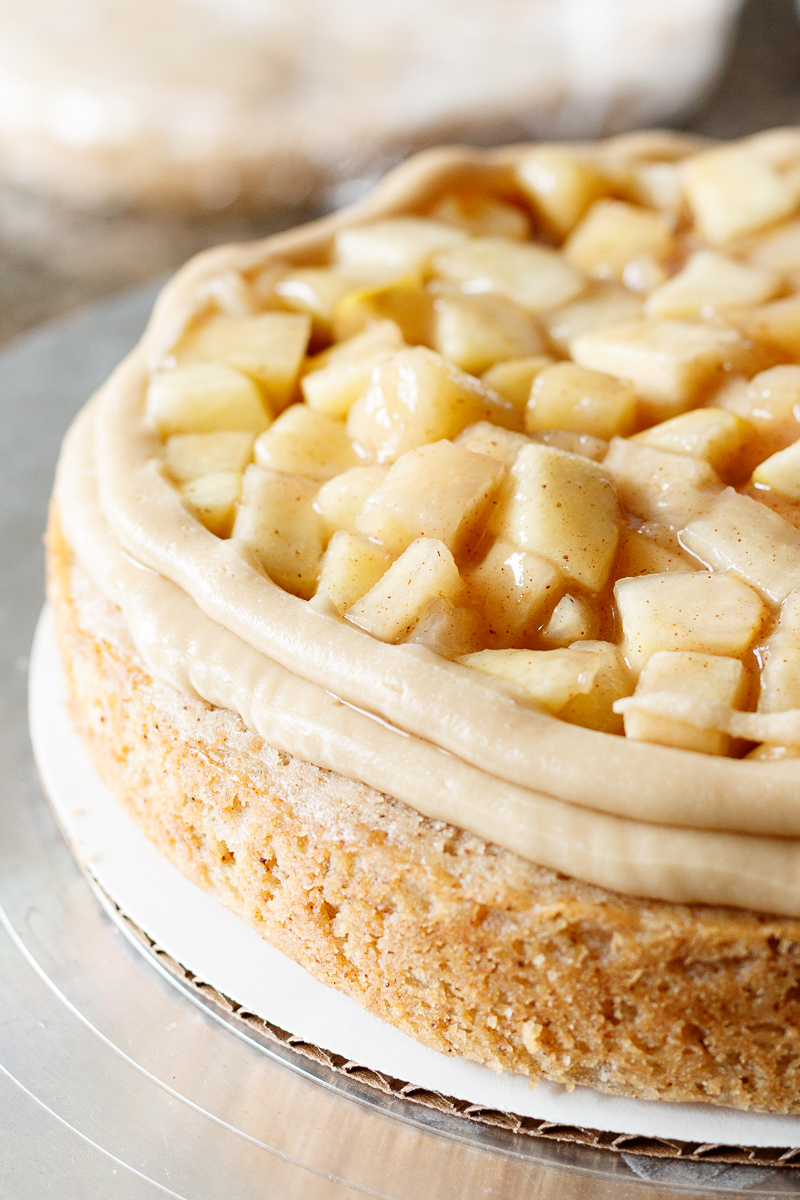 unfrosted cake layer, showing an edge dam of caramel frosting and apple pie filling in the center