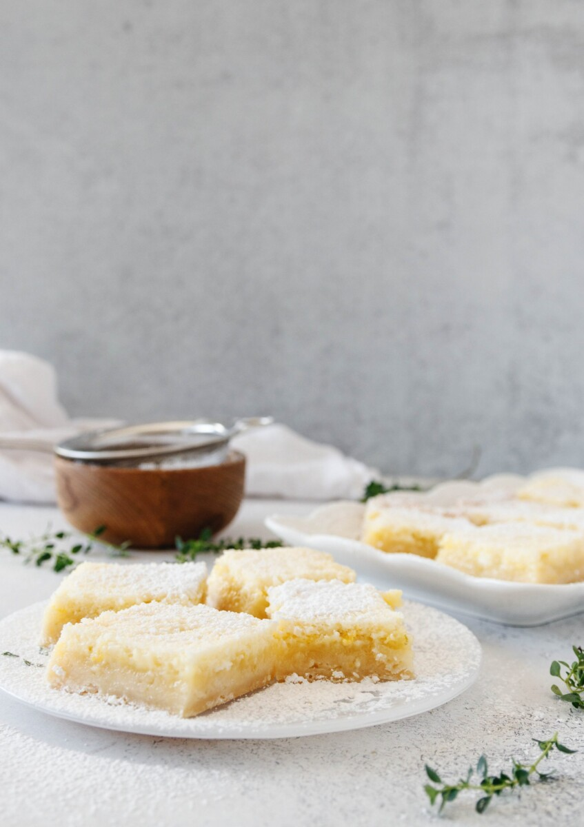 creamy lime bars on a plate with a small strainer of powdered sugar in the background, lemon thyme garnish