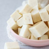 closeup of the easy cardamom fudge, cut into pieces and piled in a pale pink bowl