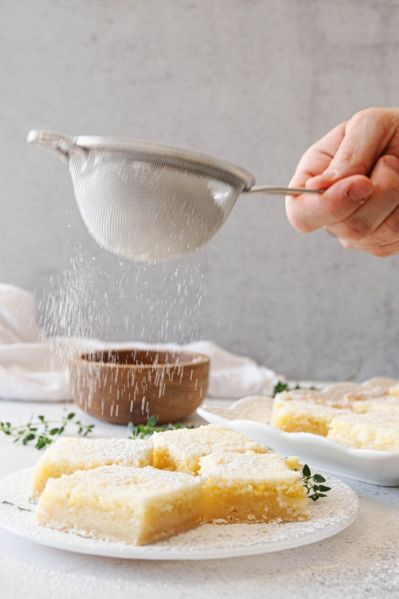 The Godfather's hand shaking a fine mesh sieve with powdered sugar over a plate of lime bars