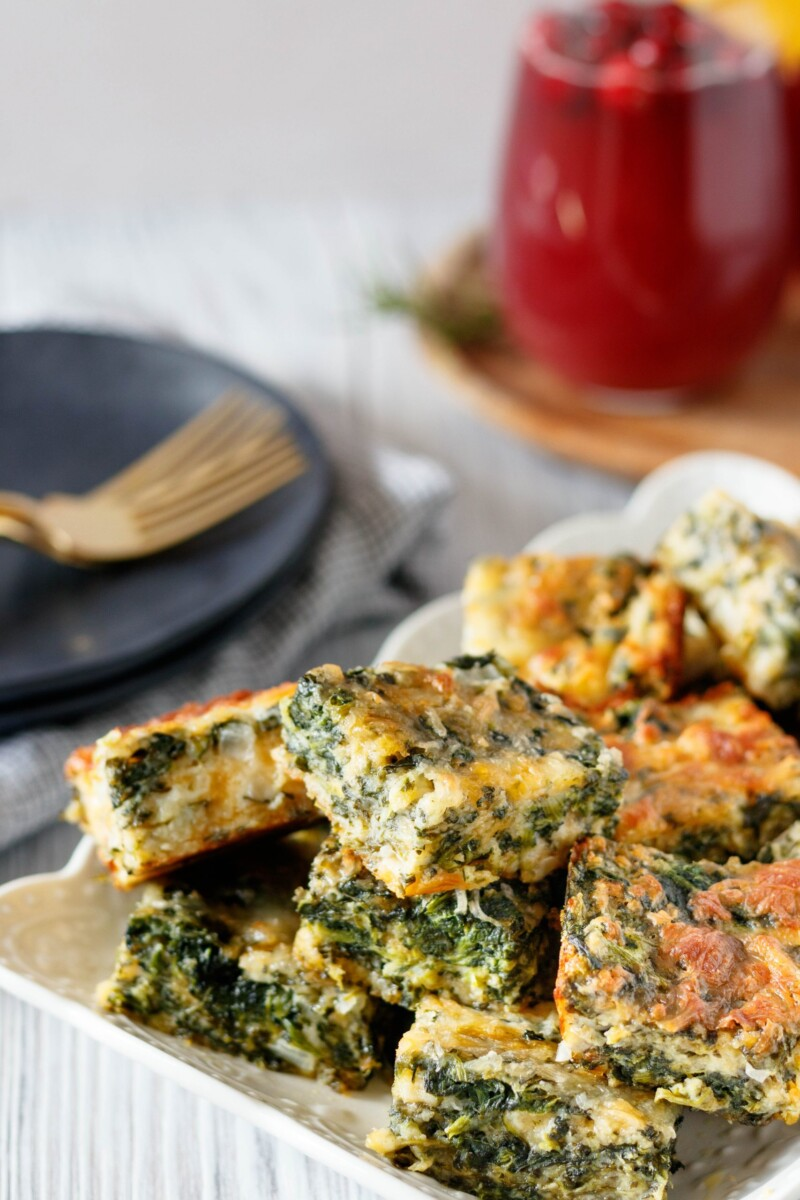 easy spinach squares piled on a plate with Christmas brunch punch in the background