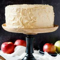 caramel apple spice cake on a black and wooden cake stand with apples in the background