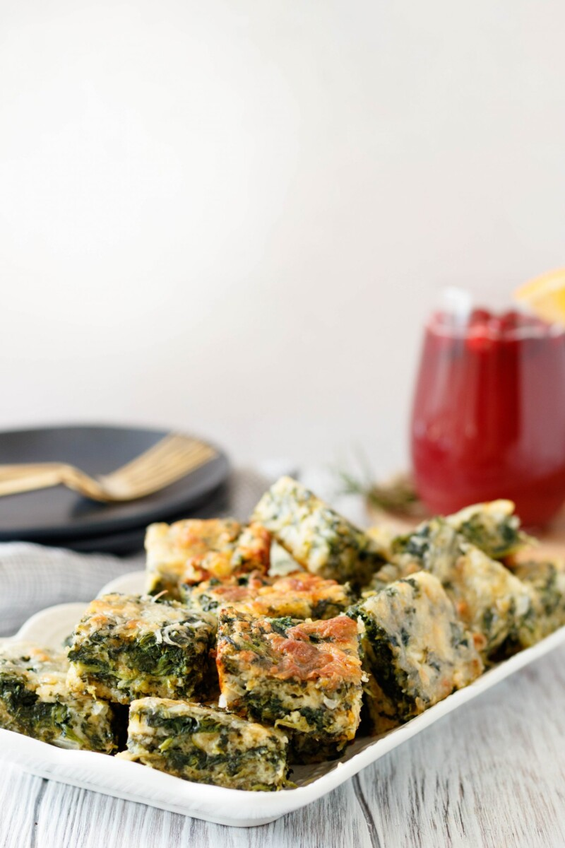 spinach cheese squares on a rectangle plate with gold forks sitting on a black plate in the background, ready to serve