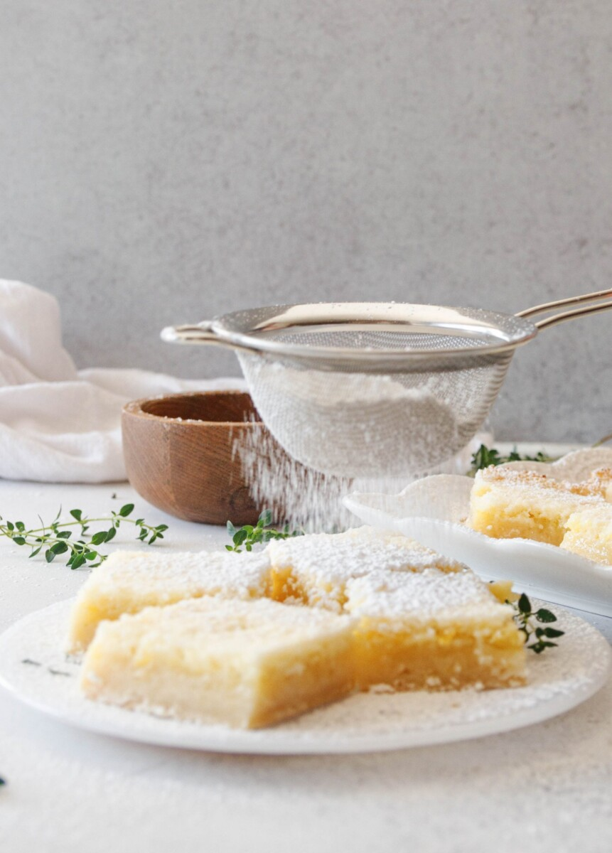 easy lime bars being dusted with powdered sugar