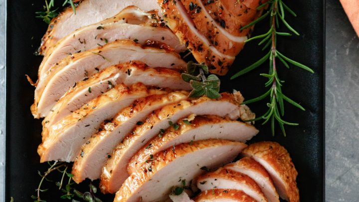top view of a sliced and plated pellet grill smoked turkey breast on a black plate with fresh herb garnish