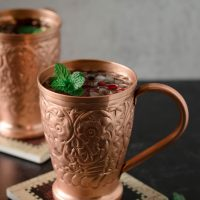angled picture of pomegranate moscow mules garnished with mint in copper mugs