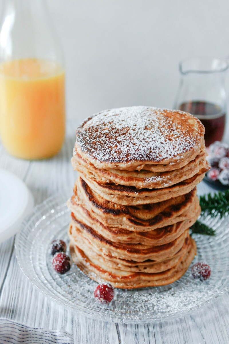 angled picture of a big stack of pancakes dusted with powdered sugar. Pancakes are on a glass plate and garnished with a few sugared cranberries.