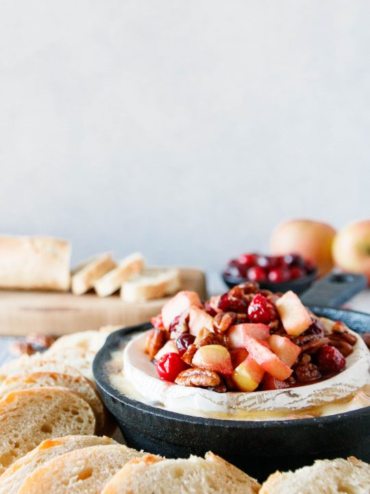 cranberry apple baked brie in a cast iron skillet with a sliced baguette and whole apples in the background