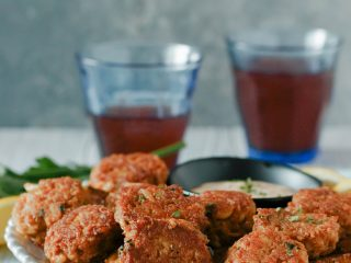 mini crab cakes on a plate with a small bowl of remoulade sauce for dipping and 2 drinks in blue glasses in the background
