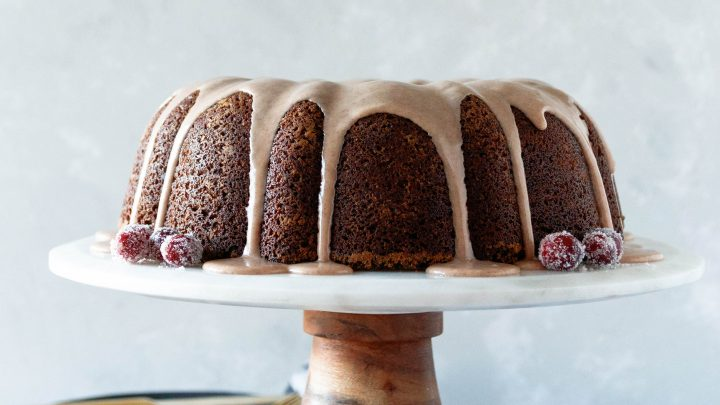 gingerbread bundt cake with cinnamon glaze on a marble and wood cake stand with sugared cranberries and greenery