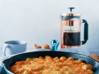 tater tot breakfast casserole made in a blue case iron skillet with a french press in the background