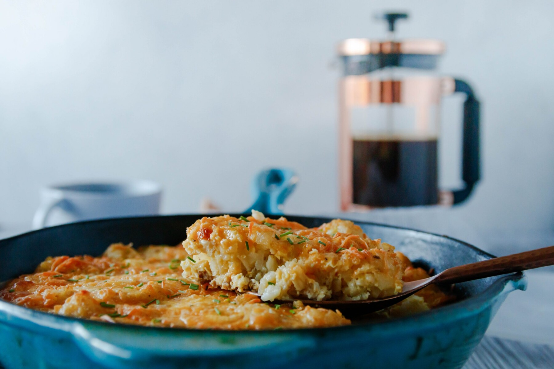 horizontal photo of a spatula lifting out a slice of tater tot casserole