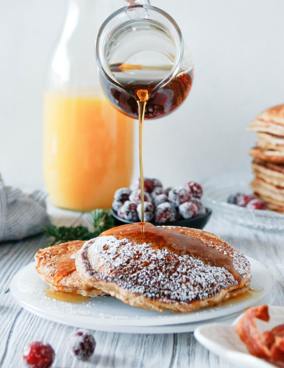 a glass pitcher pouring syrup on plated eggnog pancakes. Orange juice in the background
