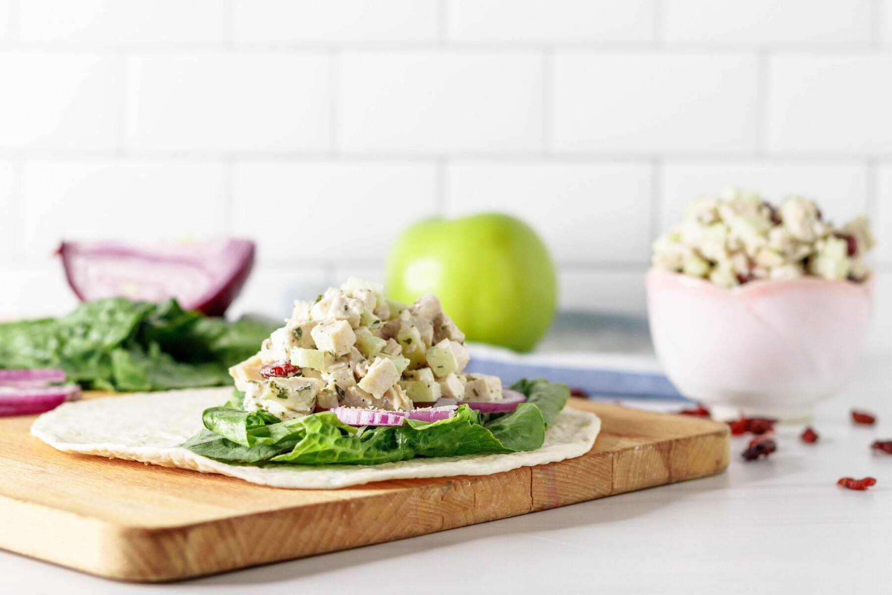 horizontal picture of the chicken salad wrap sitting on a wooden cutting board with an apple, lettuce, cut onion, and extra chicken salad in the background