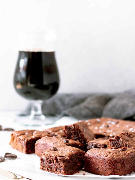 fudgy stout beer brownies cut and ready to serve on a piece of parchment paper. There's a stout beer and a dark napkin in the background