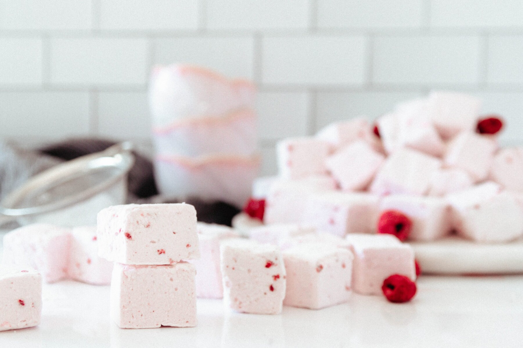 scattered marshmallows on a white surface with flower shaped pink bowls stacked in the background