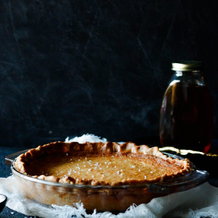 whole salted whiskey honey pie sitting on a fringed napkin. The background is black and you can see a partial outline of a jar of honey