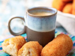 angled view of two croquetas de pollo on a colorful saucer with a small cup of cuban coffee
