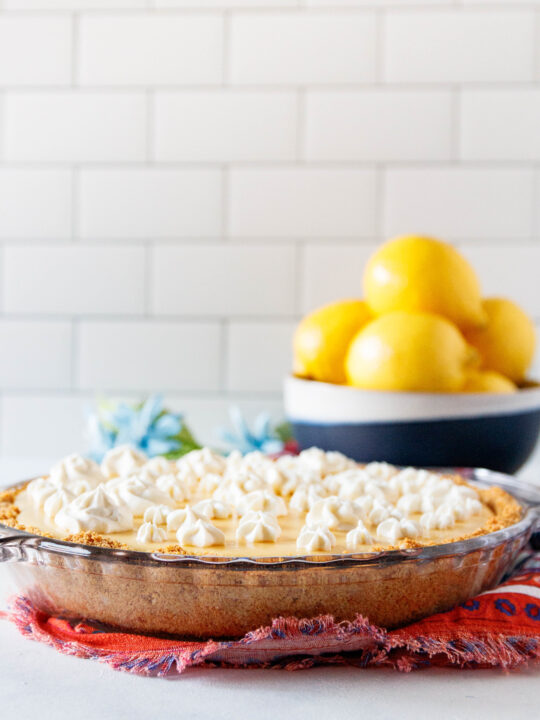 ready to slice lemon pie on a colorful napkin. There's a bowl of lemons in the background and the pie is dotted with swirled of whipped cream