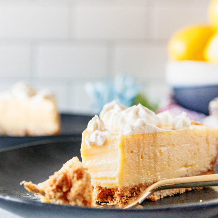 close up picture of a slice of creamy lemon pie with a bite cut out of it. This shows the smooth texture of the pie filling and the contrast with a par-baked graham cracker crust