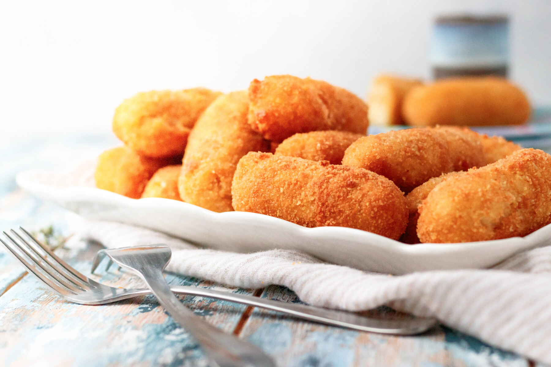 chicken croquettes piles on a white rectangle serving plate ready to enjoy!