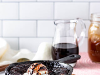 hot fudge cake sitting on a cork trivet with a white subway tile background