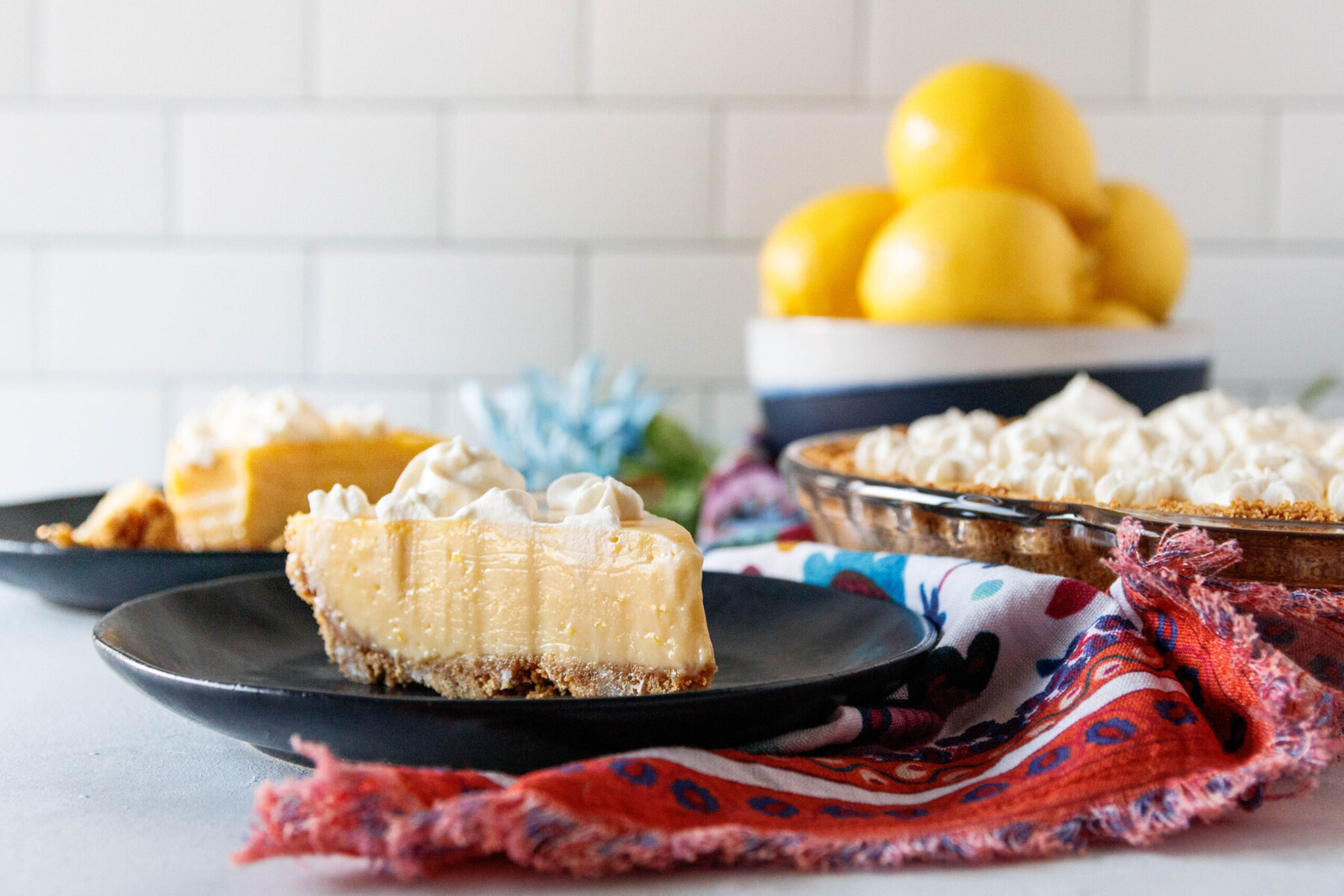horizontal image showing a slice of lemon pie on a black plate with a bowl of lemons in the background