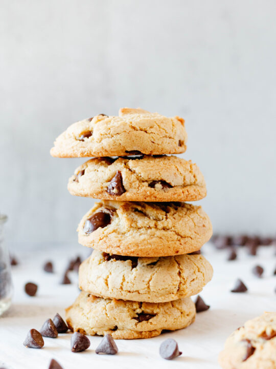 stack of 5 chocolate chip cookies with scattered chocolate chips around the stack