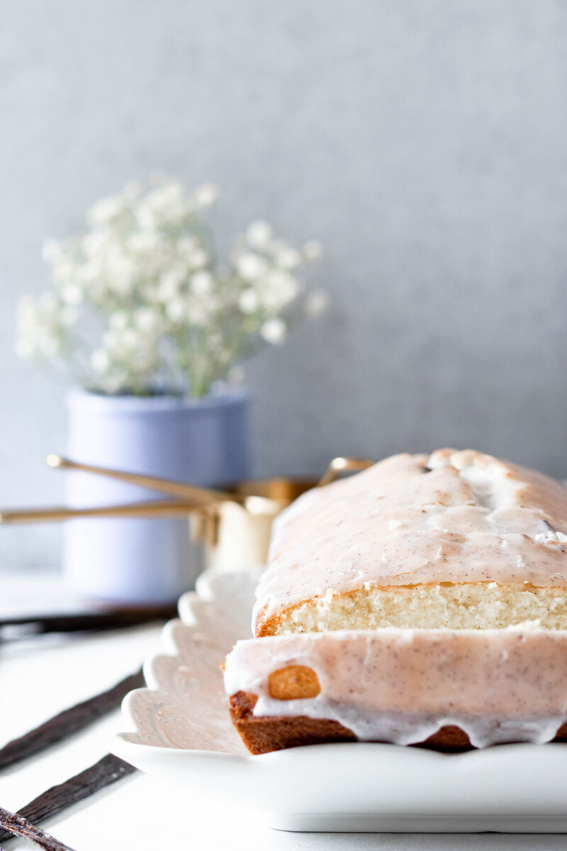 styled photo of the sliced cake loaf with the cake off to the right of the frame and a small jar of baby's breath in the rear left
