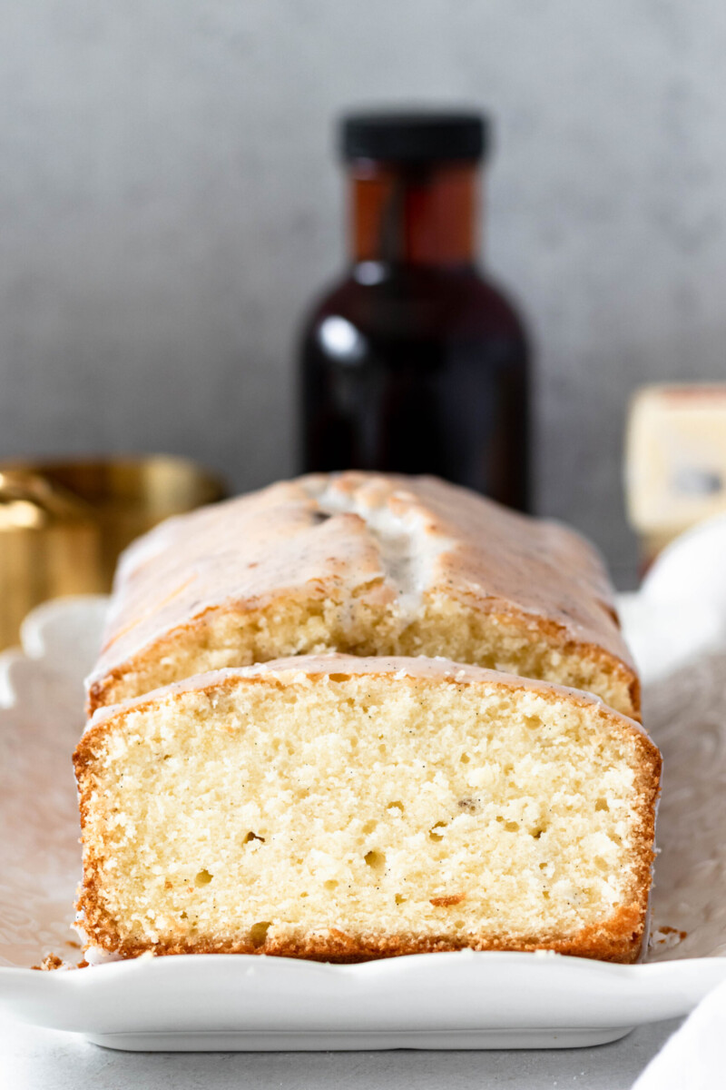 slice of vanilla bean pound cake on a white platter, propped up against the rest of the loaf