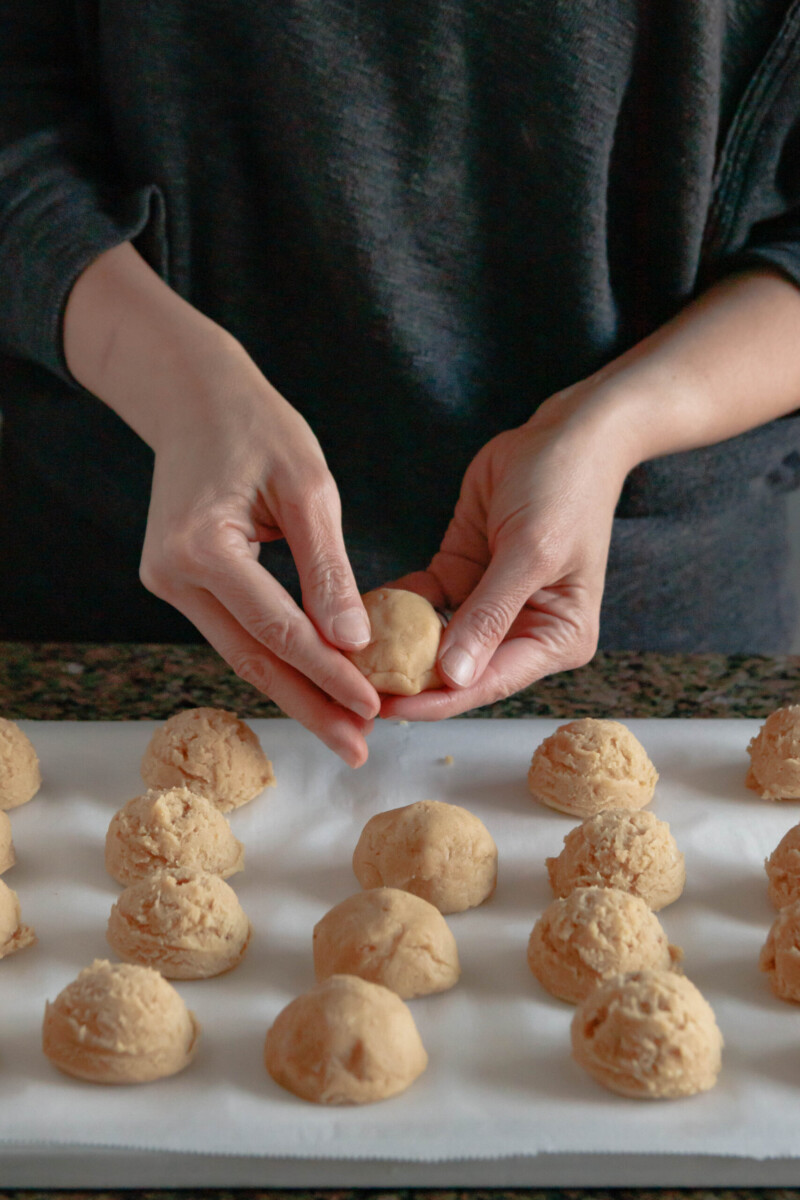 hands shaping cookie dough around pastry cream filling