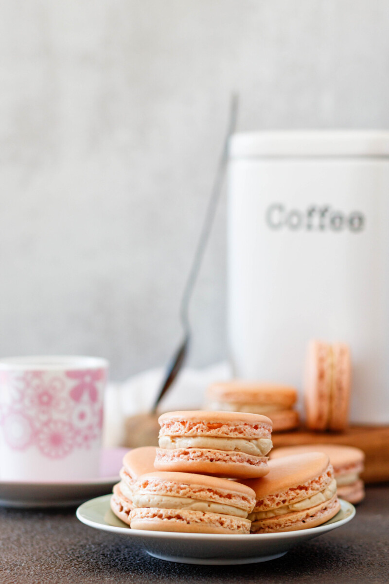 macarons on a serving plate with a cannister of coffee in the background